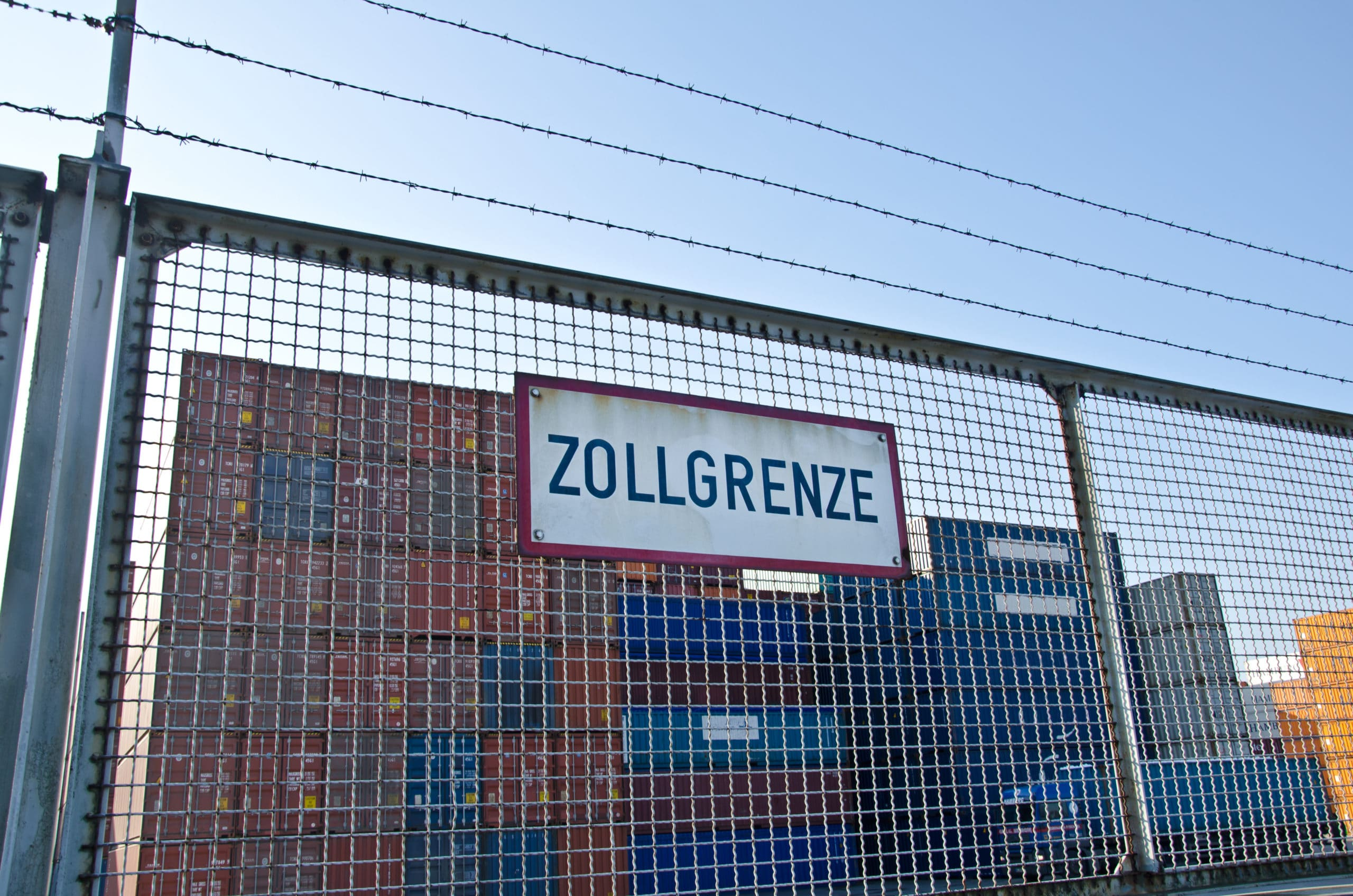 Stacheldraht Zaun mit Schild Zollgrenze vor Container Lagerplatz